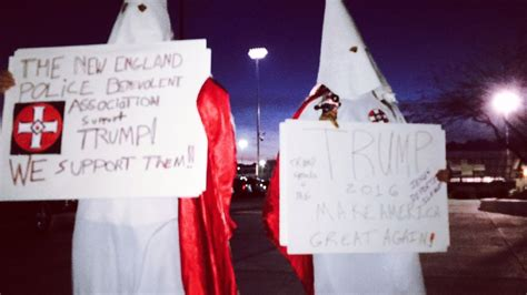 Men dressed in KKK clothing stand in front of Cimarron